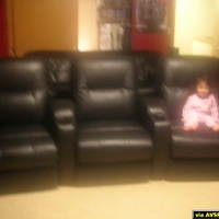 My daughter sittingin our new theaterseats