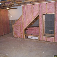 Here the framing and insulation are in.  The holes under the stairs are for a build in dvd case and equipment rack.