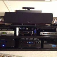 "Close up of the AV Rack: Denon AVR 4311ci; Emotiva XPA-5; Oppo 103; X-Box 360, w/ Kinect (resting on a floating shelf above speaker); Comcast STB; APC-J25B;  *** the shelves of this AV rack are tempered glass w/ a weight rating of 175 lbs (top shelf) & 60lbs for the middle & lower.  So, in order to support the 130+ lbs of gear on the bottom shelf; I had to bolster it w/ two sheets of 5/8th"" plywood (cut to fit) under the bottom shelf . . . and because the glass is tempered black; you are not able to see the wood.  Anyway, blah, blah, blah."