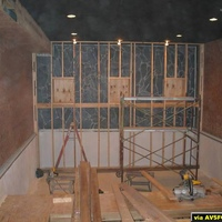 This shot shows the framed wall with the speakers boxes.  The screen speakers will be mounted behind the screen as in a commercial theater.  The box you see against the left wall at the ceiling is where the AC duct was run for the living room...