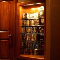 Media bookcase with glass shelves located in alcove on the side of the theater.