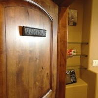 "knotty alder entry door features the ""Mancave"" signage with glass candy display in the background."