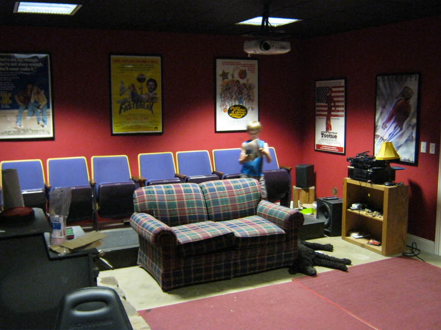 This the the back of the theater.  I am especially proud of the late 70s basketball themed movie posters on the back.  Seating is from a high school auditorium in Columbia, MO.  Projector is an Epson Home Cinema 720.  Rugs are from Wal-Mart.  The poodle is Moe.