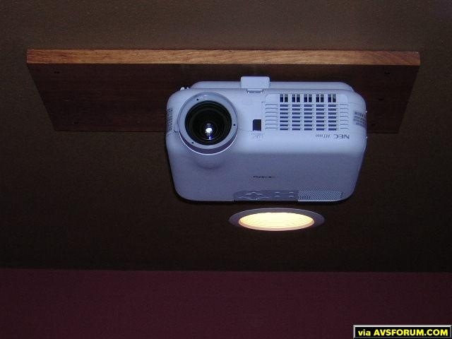 Cieling height was short in my basement so I used pine shelving material stained and varnished to match trim in room to mount projector on.  Projector is mounted using bolts.  Holes in wood were counterbored to flush the bolt heads then board was...