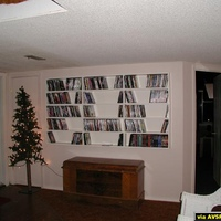 Outside rear wall with DVD shelves and equipmetn cabinet access door on the left behind the Christmas tree.