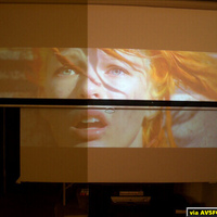 "This is a photo of a 100"" Highpower on top of my old BOC screen directly behind. Projector is ceiling mounted. This photo is a split screen shot with a 180W light on in the room. The light is on the left of the screen and in front of it. The..."